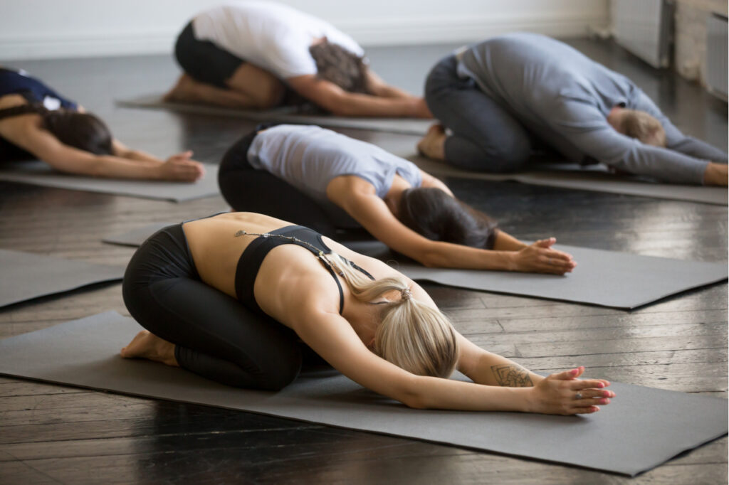 Group of young sporty people practicing yoga lesson with instructor.