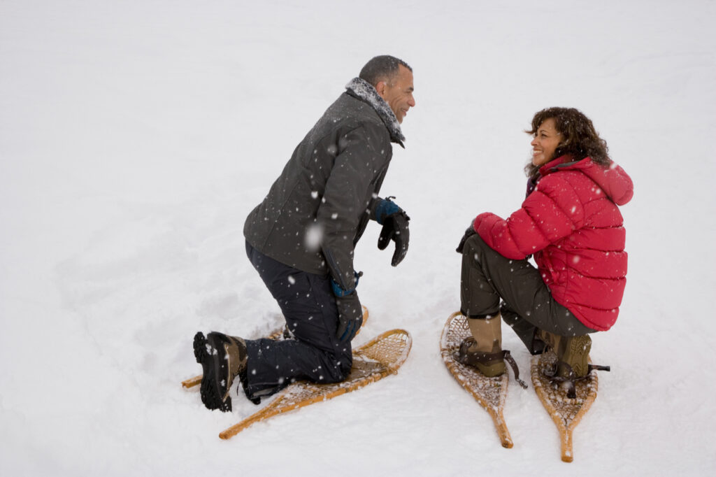 Couple crouching in the snow wearing snowshoes as a snow sports.