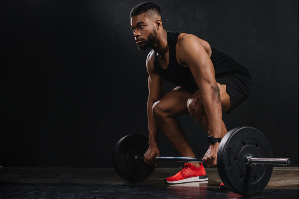 Muscular young sportsman lifting barbell and looking away on black.