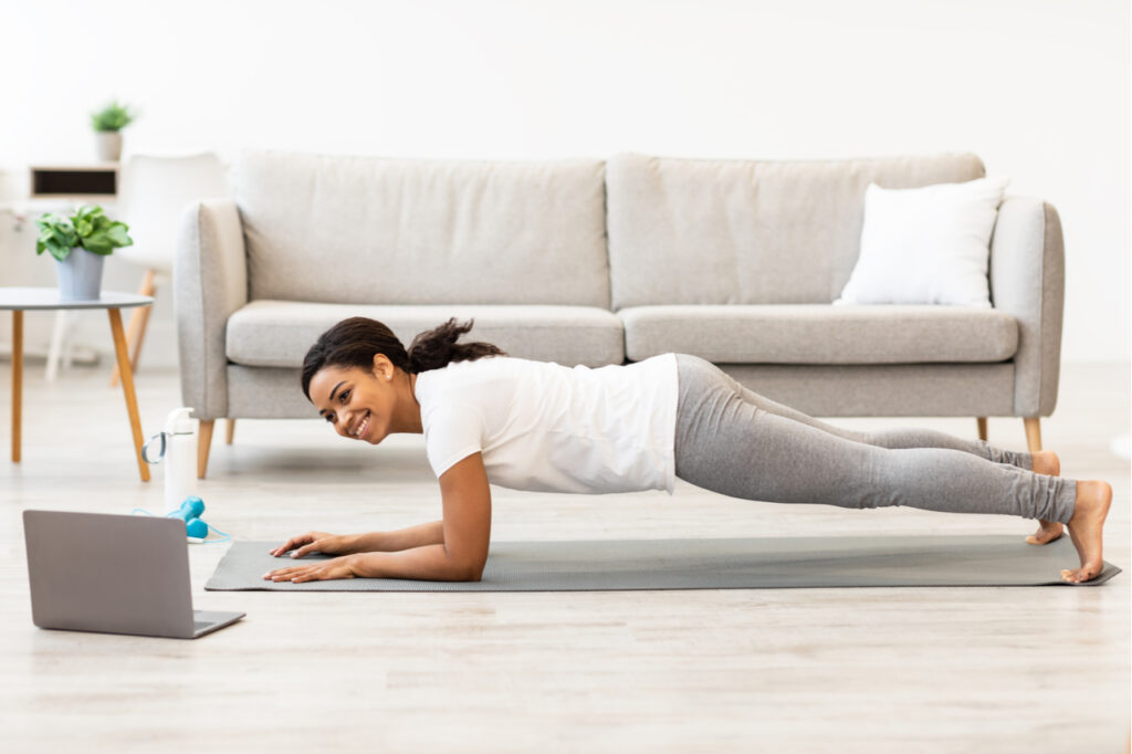 Woman exercising at home while watching an online tutorial as one of the fitness trends.