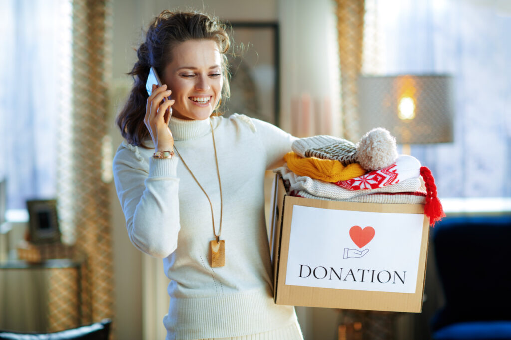 Woman in white sweater and skirt with donation box with old warm clothes talking on a cell phone at modern home in sunny winter day.