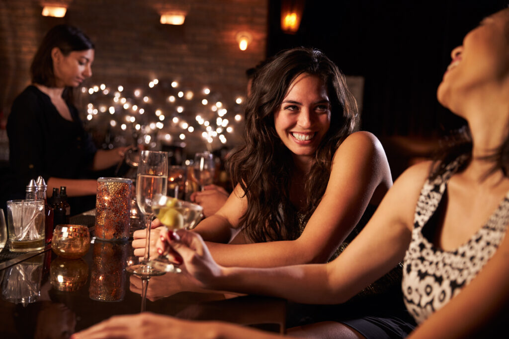 Female friends enjoying night out at cocktail bar.
