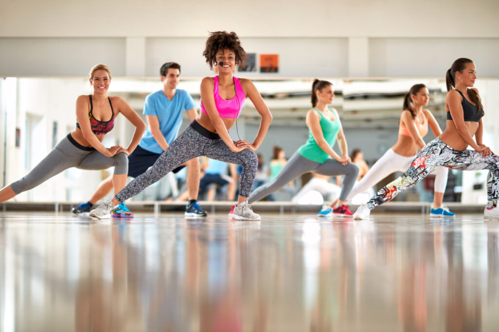 Young black curly trainer with group training aerobic at gym.