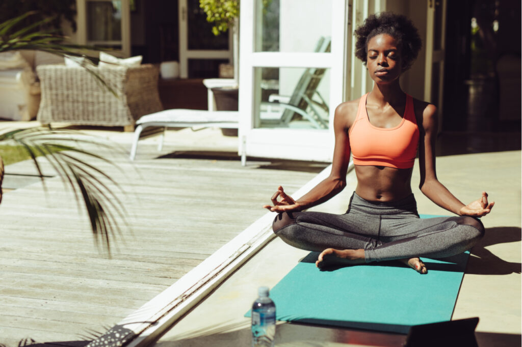 Healthy woman sitting on yoga meditation at home on yoga mat. Fitness woman in sportswear meditating in lotus yoga pose by the poolside.