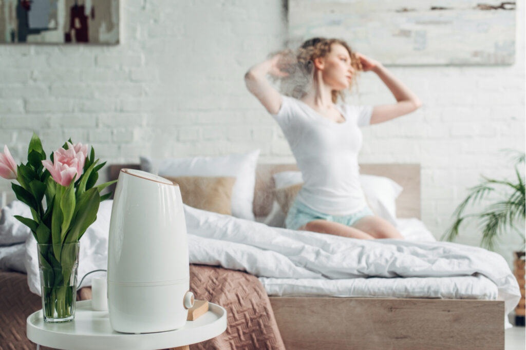 selective focus of girl sitting in bedroom with tulip flowers and air purifier spreading steam