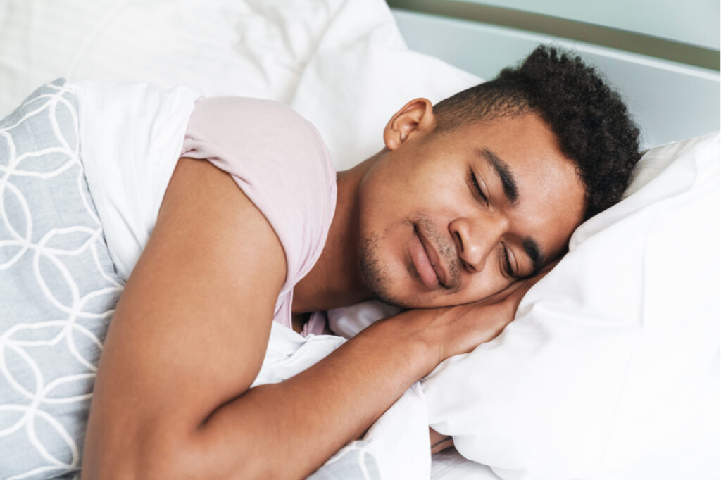Guy in the morning in bedroom lies in bed.