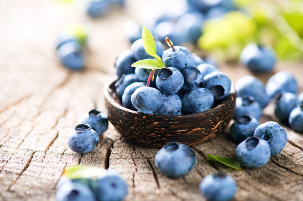 Juicy and fresh blueberries with green leaves on rustic table.