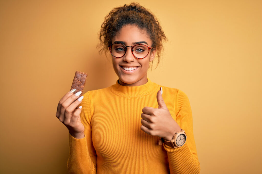 Woman eating IQ bar with her thumbs up.