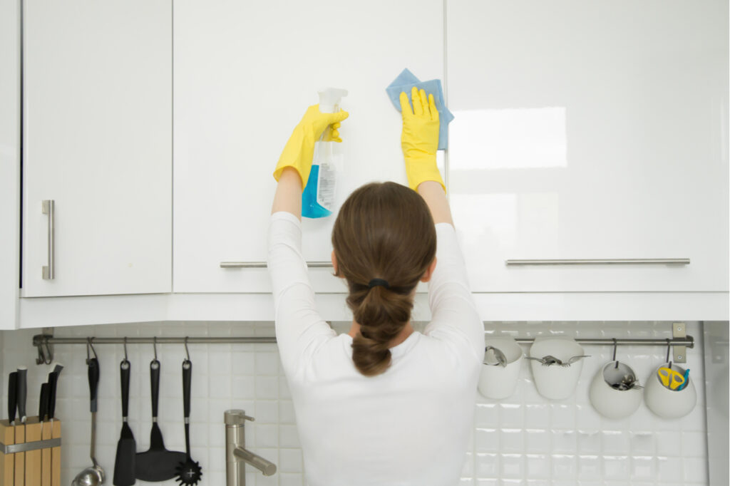 Woman cleaning a surface of white kitchen wall cabinet.