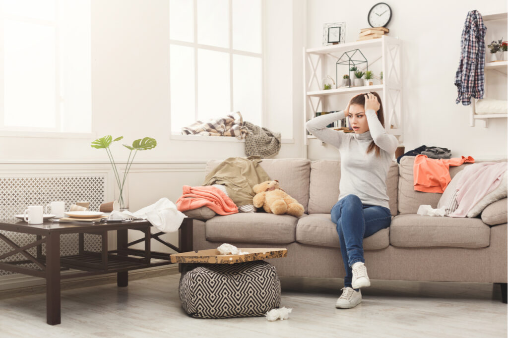 Desperate helpless woman sitting on sofa in messy living room. Young girl surrounded by many stack of clothes.  Her physical environment is messy.