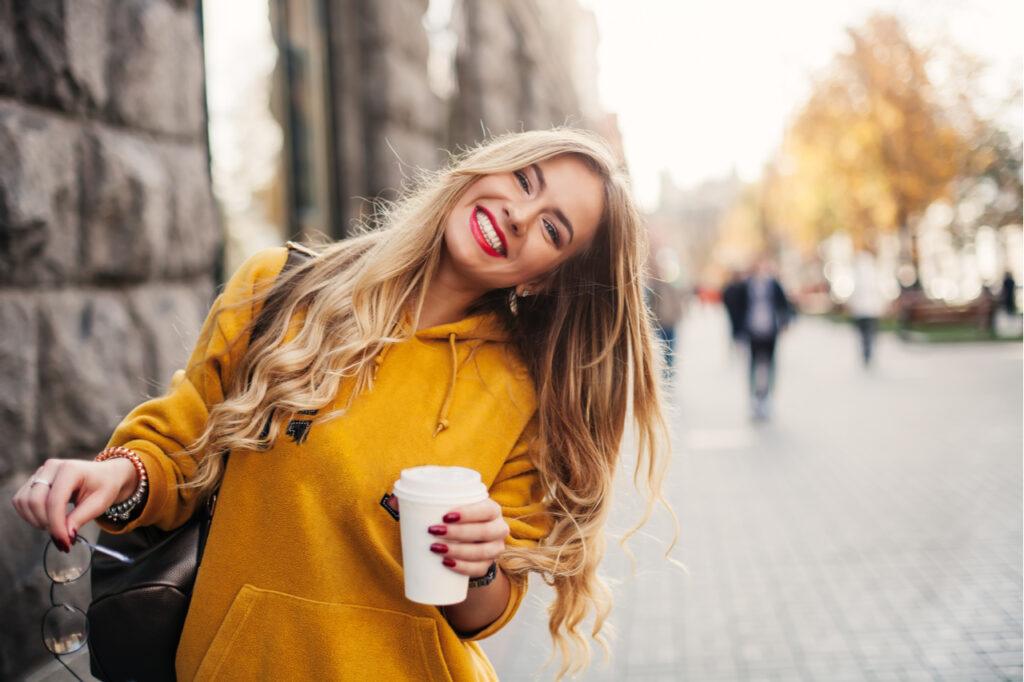 Stylish happy young woman wearing bright yellow sweatshirt holding coffee to go.