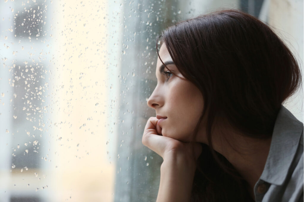 Depressed young woman near window at home with seasonal affective disorder.