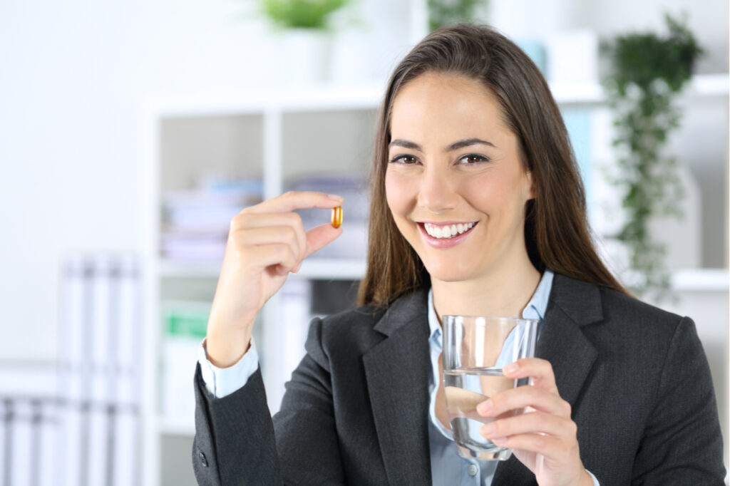 Woman shows vitamin pill and water glass at the office.