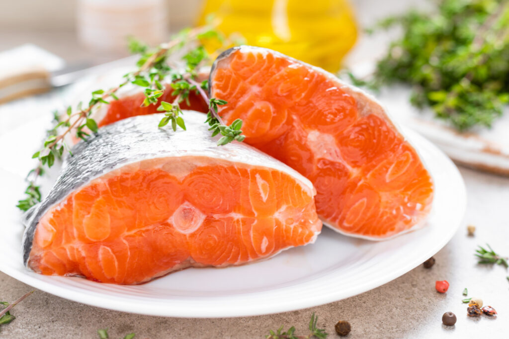 Fresh raw salmon fish steaks on white kitchen for National Nutrition Month.