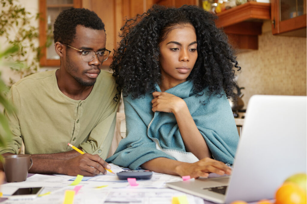 Couple doing paperwork together, sitting at kitchen table with piles of papers for financial independence.
