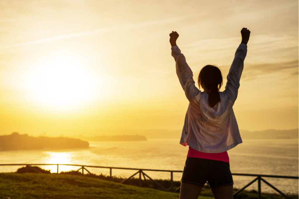 Successful sporty woman raising arms towards golden beautiful sunset as a way on how to motivate yourself to work out.