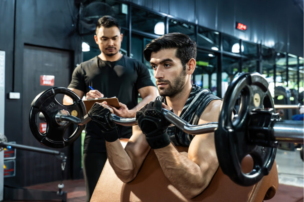 Man wearing workout gloves while practicing weight lifting exercise with professional sport coach.