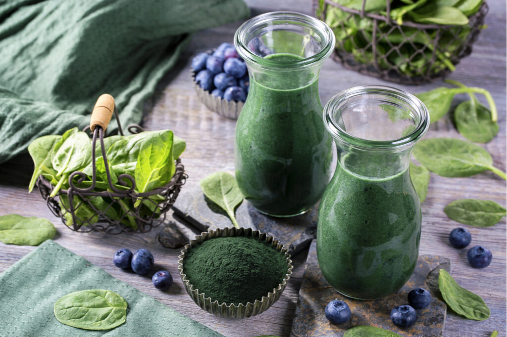 Green smoothie with spirulina, spinach and blueberries.