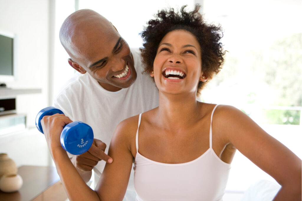 Man smiling at woman exercising with weights at home.