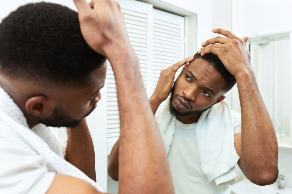 Man checking for thinning hair in mirror at bathroom needing hims hers hair loss.