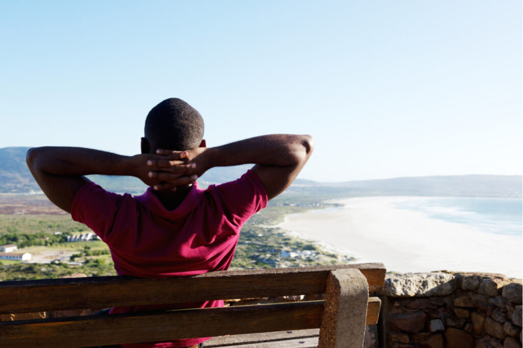 Rear view portrait of young african man sitting relaxed on a bench with his hands behind head, young guy on vacation.