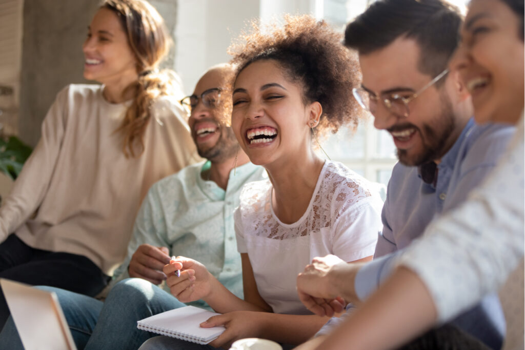 Overjoyed multiracial young people sitting in row having fun.