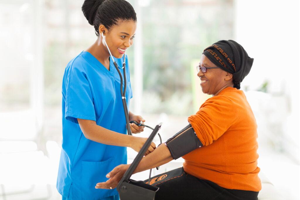 Smiling nurse checking senior patient's blood pressure.