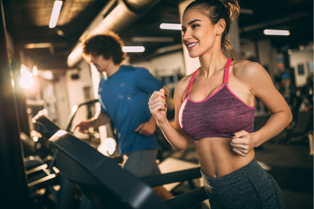 Horizontal photo of attractive woman jogging on treadmill at health club for kidney health.