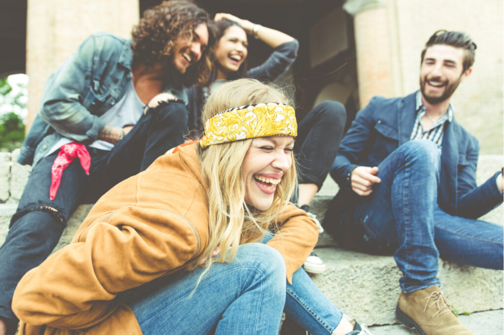 Group of four friends laughing out loud outdoor.