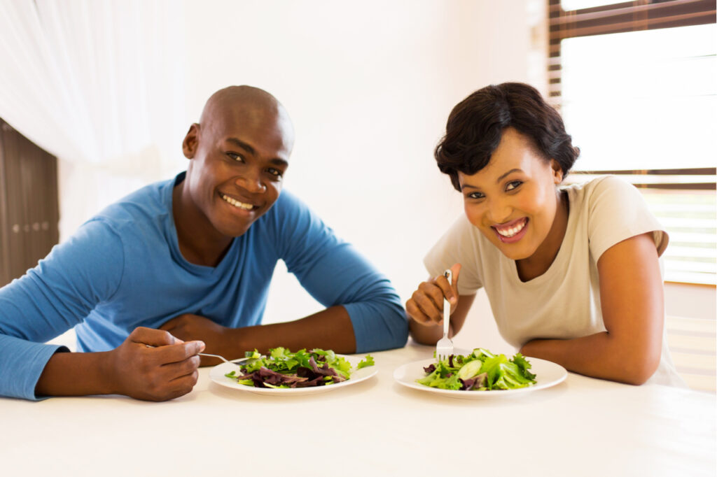 Couple eating healthy salad for lunch counting macros.
