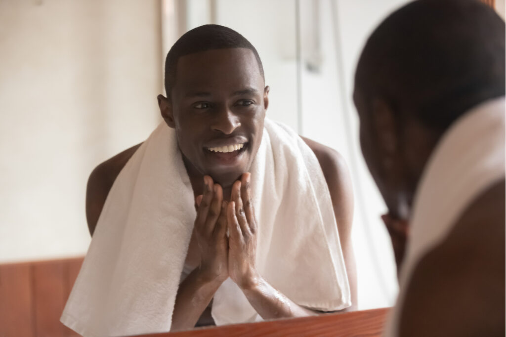 Man with a towel on shoulders standing front of the mirror knows how to get rid of acne fast.