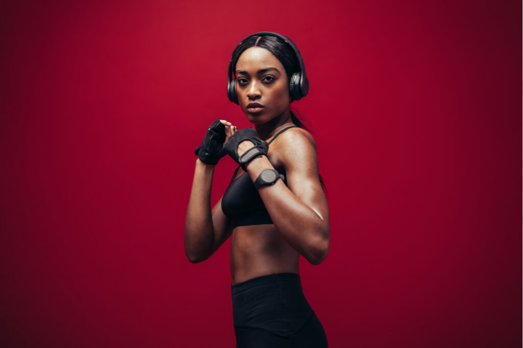 Woman wearing boxing gloves posing in combat stance looking at camera.
