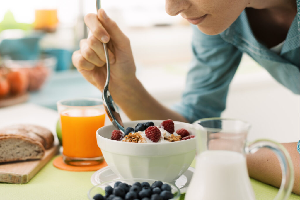 Woman having an healthy delicious breakfast at home as part of multiple sclerosis diet.