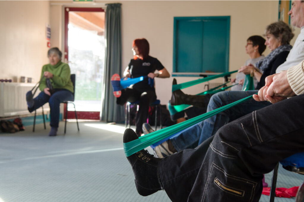 Occupational therapy instructor provides training exercises for patients at health center with multiple sclerosis diagnosis.