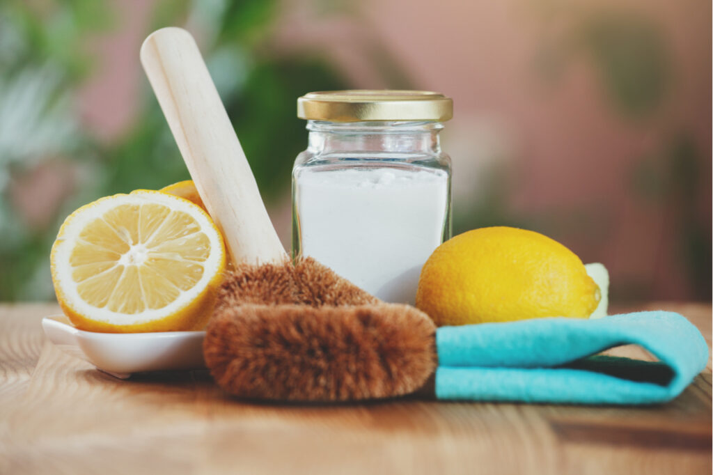 eco-friendly house cleaners, baking soda, lemon, bamboo cleaning brush and green cloth on wooden table, non toxic cleaning
