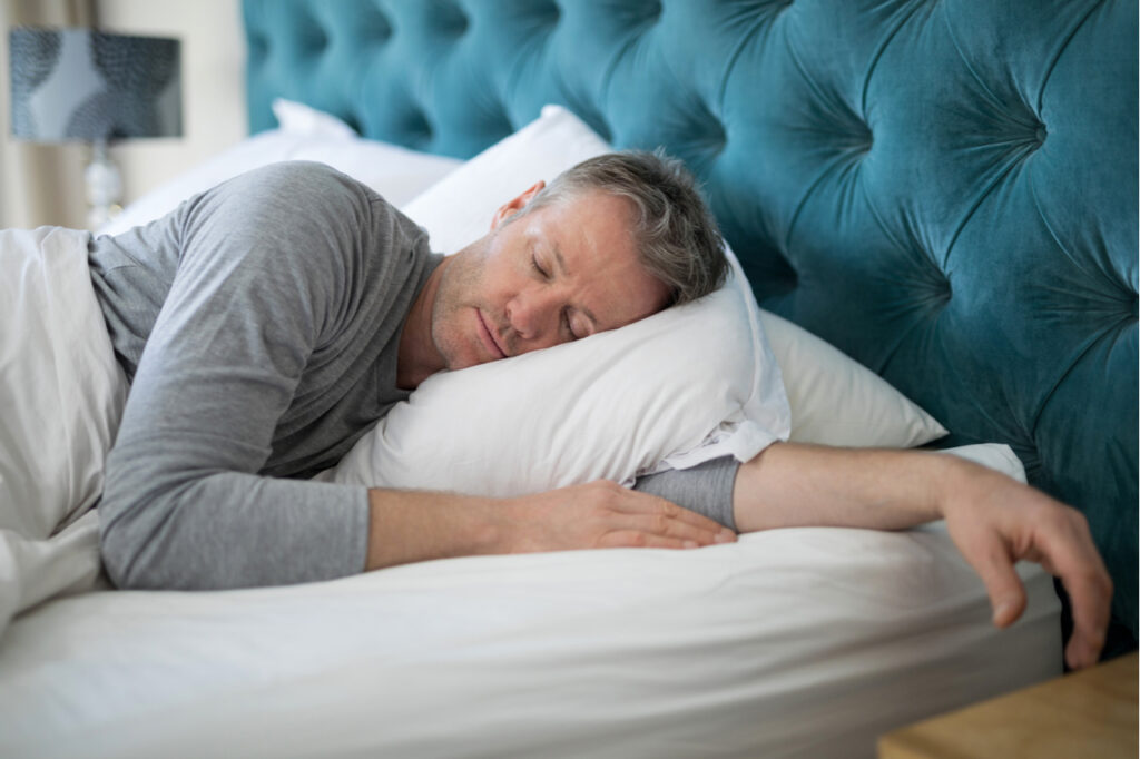 Man sleeping on bed in bedroom at home from lack of sleep.