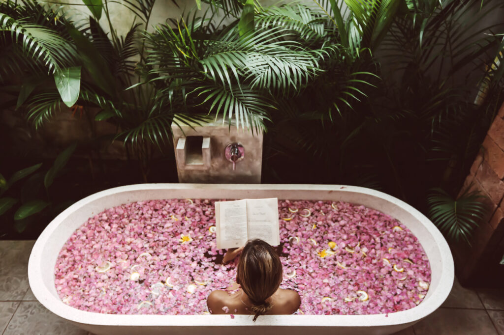 Woman reading book while relaxing in bath tub with flower petals.