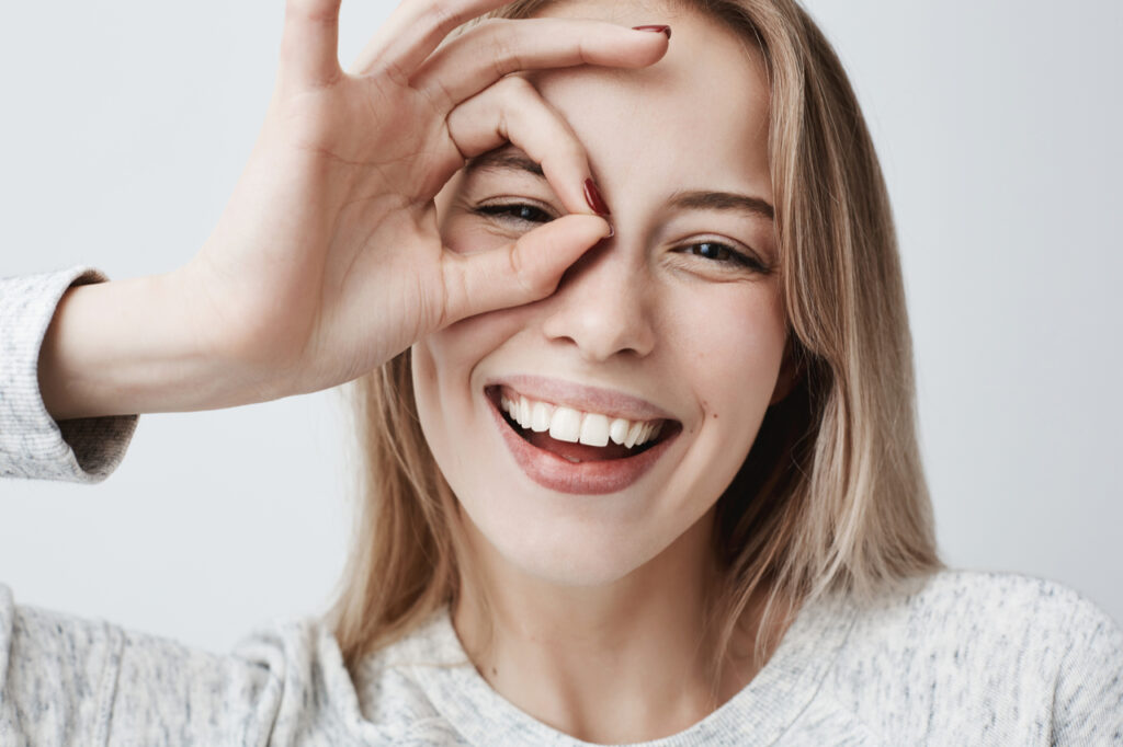 Woman looking at the camera smiling with her fingers in okay gesture.
