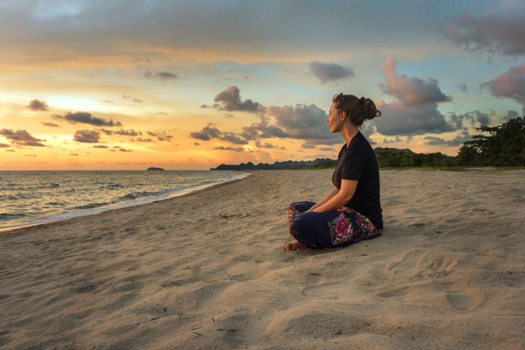 Woman sitting on beach sand and relaxing at sunset time.
