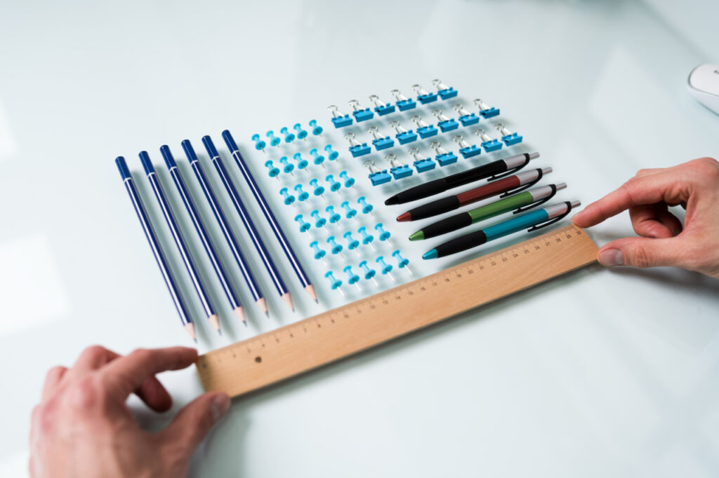 A person's hand arranging office supplies on the table.