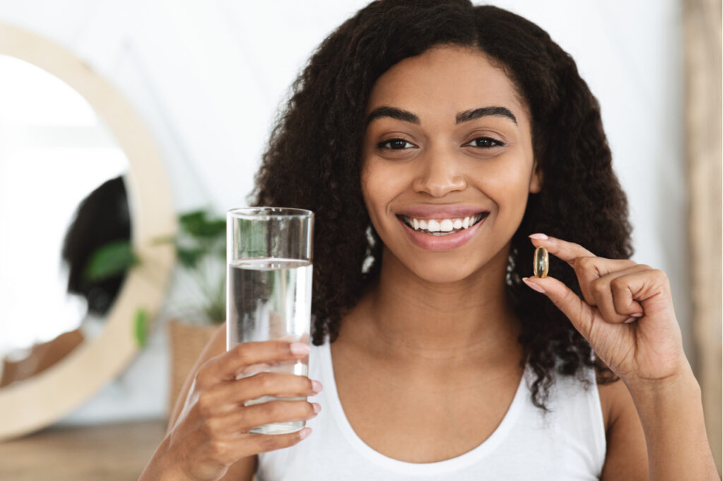 Smiling woman holding a glass of water and a pill.