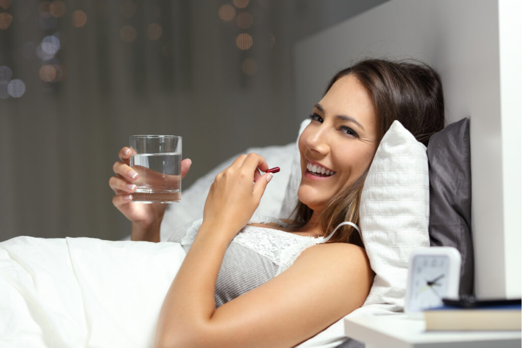 Happy woman taking onnit total human at night.