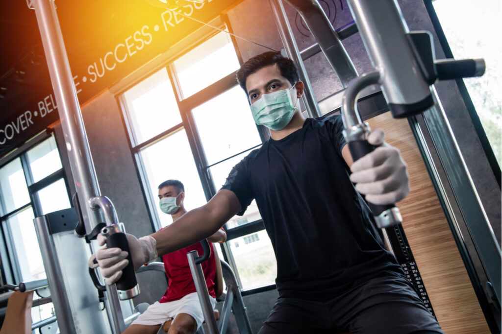Asia men working out wearing surgical mask & latex rubber gloves.