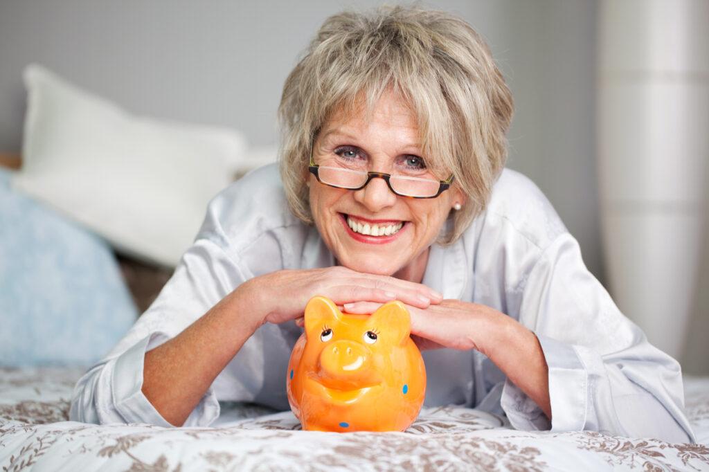 Conceptual portrait of happy senior female lying on bed with piggybank.