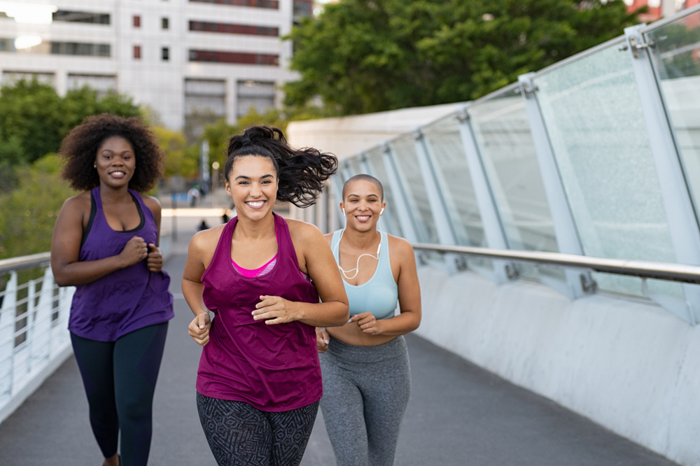 women jogging together on city bridge. Healthy girls friends running on the city street to lose weight.