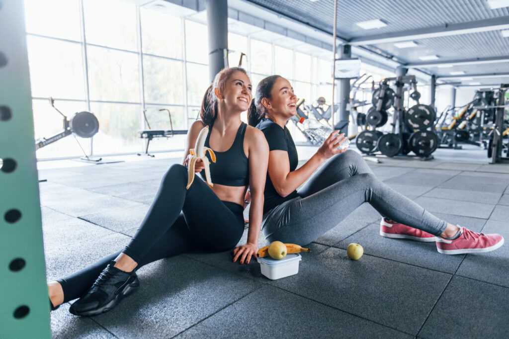 Two female friends in sportive clothes is in the gym earing fruits and taking a break.