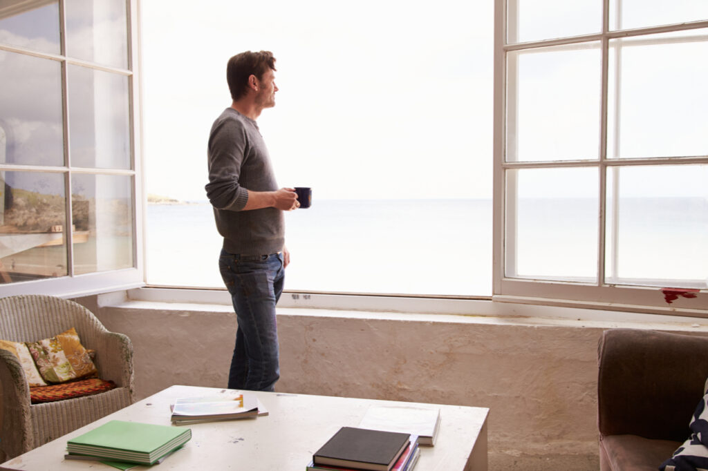 Man Standing At Window And Looking outside.