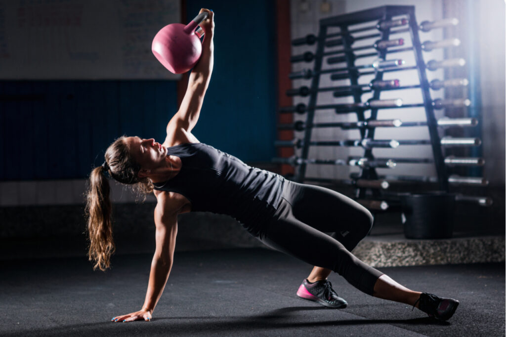 Woman athlete exercising with kettlebell indoors.