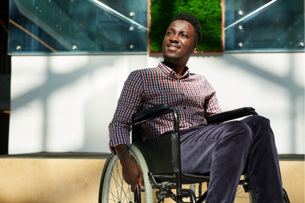 Man in wheelchair looking away and smiling at modern office.