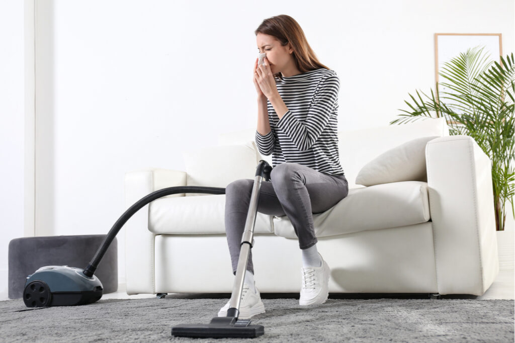 Woman suffering from dust allergy while vacuuming house that needs a healthy mind and body.